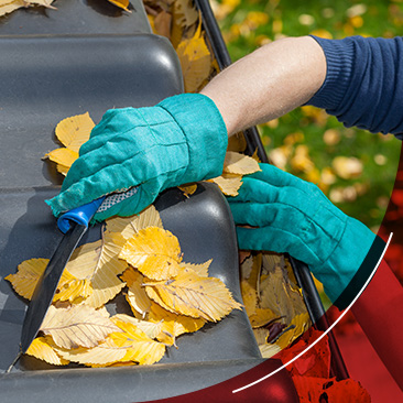 person clearing leaves from gutter